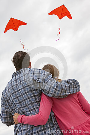 Free Man & Woman Couple Flying Red Kites Royalty Free Stock Photo - 38485465