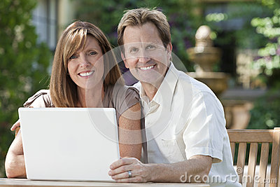 Man & Woman Couple Using Laptop Computer In Garden