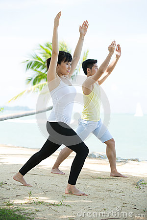 Man and Woman doing yoga on beach.