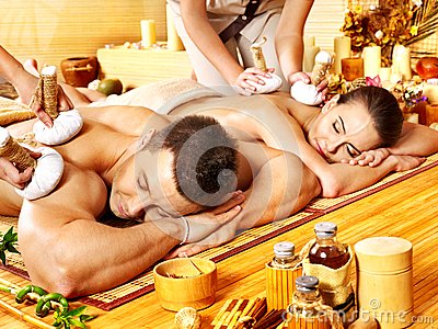 Man and woman getting herbal ball massage in spa.