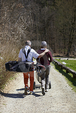 Man and woman golfer walking on a golf course
