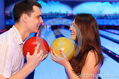 Man and woman hold balls in bowling