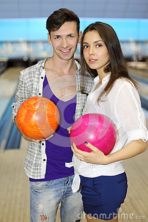 Man and woman hold balls in bowling club