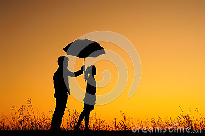 Man and woman hold umbrella in evening sunset