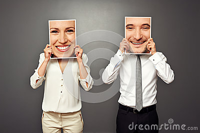 Man and woman holding smiley faces