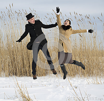 Man and woman jump on lake beach