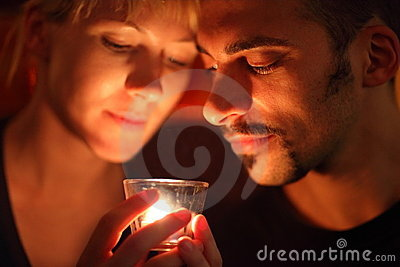 Man and woman keeping glass candle and looking