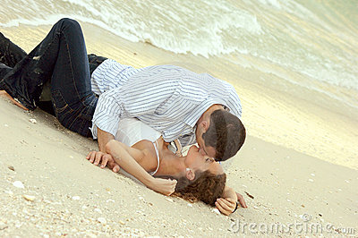Man and woman kissing on beach in wet clothes
