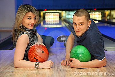 Man and woman liewith balls for bowling