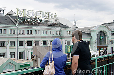 Man and woman look at the building of the Belarusian railway station in Moscow Editorial Photography