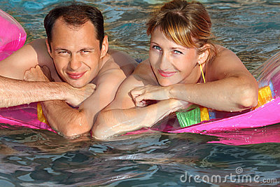 Man and woman lying on an mattress in pool