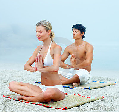 A man and a woman meditating together at the beach