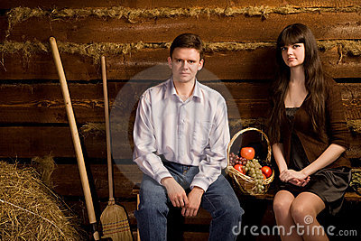 Man and woman near basket of fruit on bench