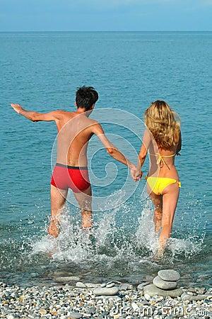 Man and woman run in the sea