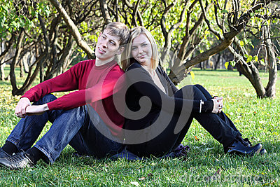 Man and woman sit on grass back to back and dreams in park