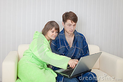 Man and woman sit on sofa with laptop