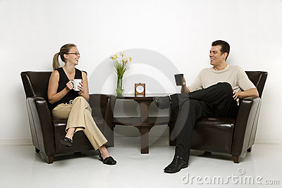 Man and woman sitting drinking coffee.