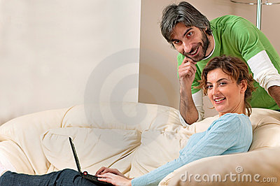 Man and Woman Smiling at Home on the Couch