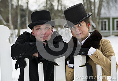 Man and woman stand behind wooden fence