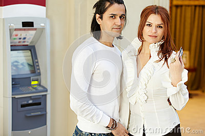 Man and woman stand near to cash dispenser