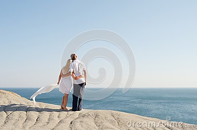 Man and woman standing arm in arm on a rock