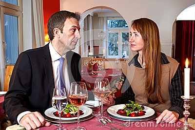 Man and woman staring at each over a meal
