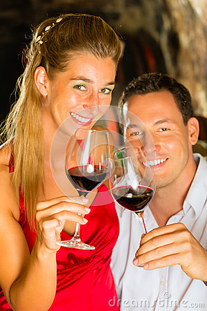 Man and woman tasking wine in cellar