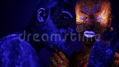 A man and a woman in the ultraviolet light caress each other. Fire and ice, two hypostases. stock video footage