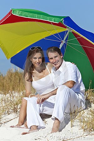 Man & Woman Under Colorful Umbrella on Beach