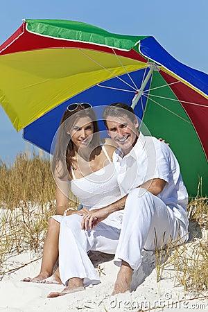 Man & Woman Under Colorful Umbrella on Beach