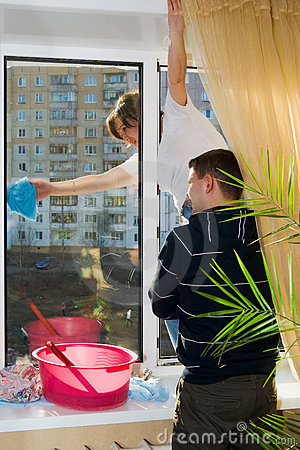 A man and woman wash a window