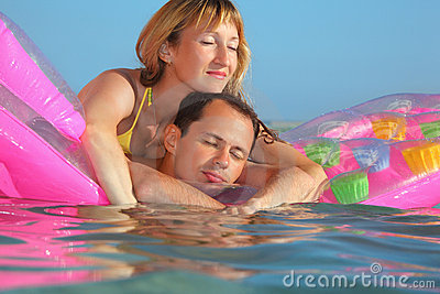 Man and women sleep on an mattress in pool