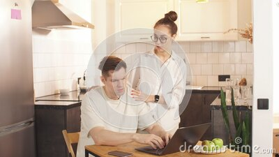 Man work from home, his careful wife next to him. stock video