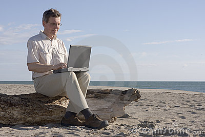 Man working with laptop on beach