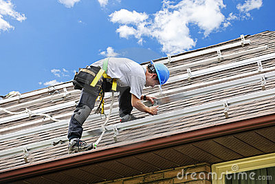 Man working on roof installing solar panels