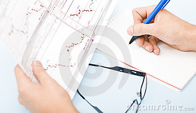 Man writing in agenda holding graphics in his hand