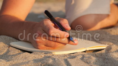 Man writing in his diary at the beach. While lying on the golden sand, close up view of the book and his hand holding a pen Shot on Canon 5D Mark II with Prime