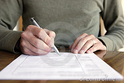 Man Writing on Paper with Pen on Table