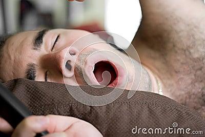 Man Yawning In Bed