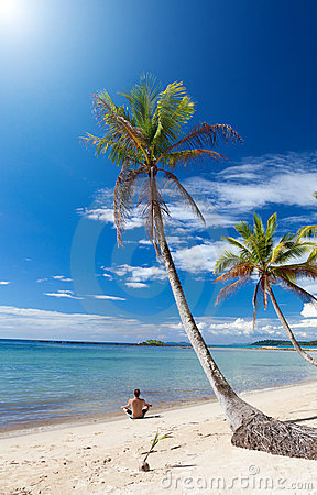 Man in a yoga posture relaxes under palm trees