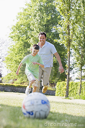 Man and young boy outdoors playing soccer