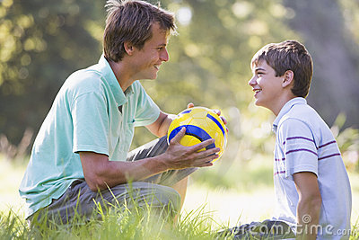 Man and young boy with soccer ball smiling