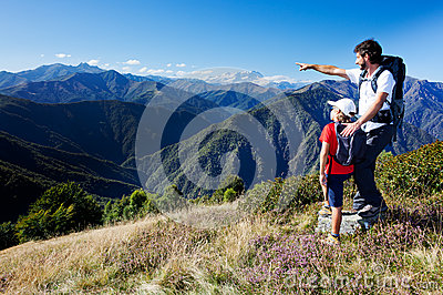 Man and young boy standing in a mountain meadow