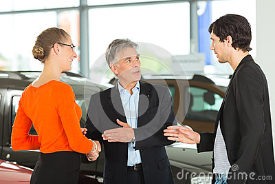 Man with young couple in car dealership
