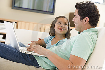 Man with young girl in living room with laptop