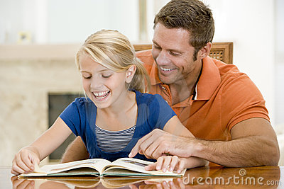 Man and young girl reading book in dining room