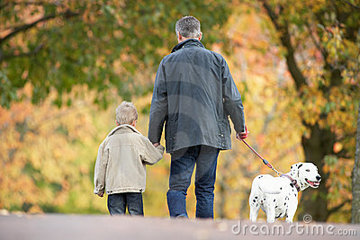Man With Young Son Walking Dog Through Park