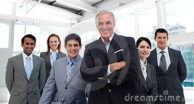 Manager with folded arms accompanied by his team