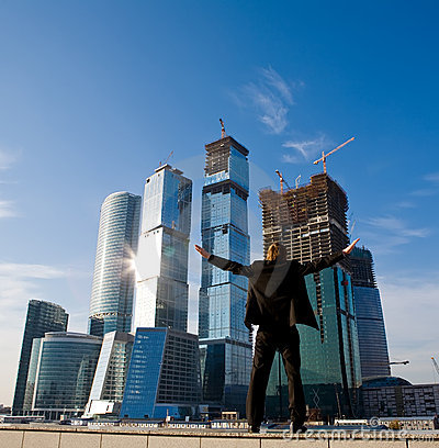 Manager with outstretched arms against skyscraper
