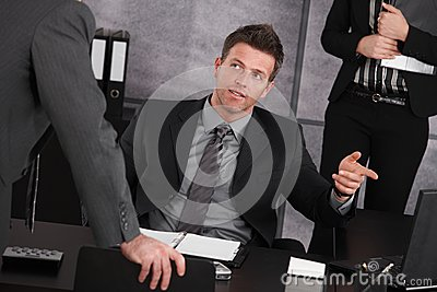 Manager sitting at desk, teaching employee